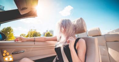 ragazza bionda con vento tra i capelli su auto decappottabile