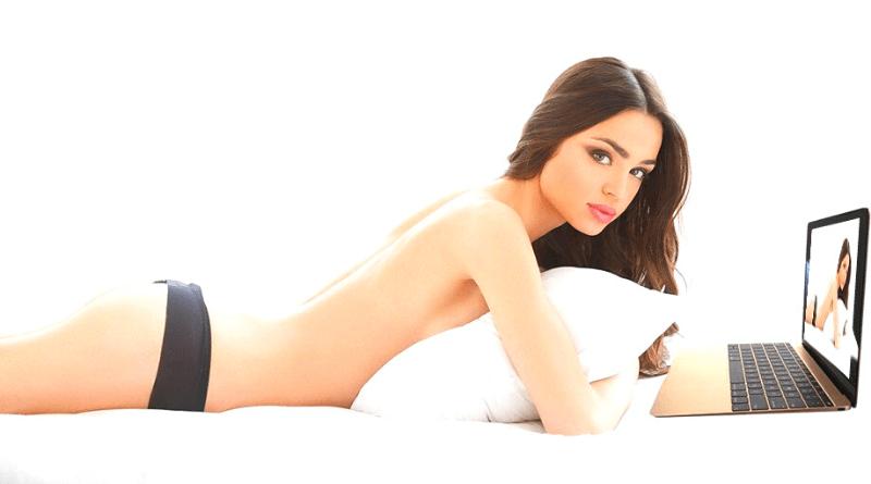 ragazza bruna in mutandine sdraiata sul letto con PC