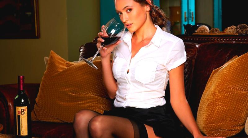 donna con calice di vino che mostra autoreggenti