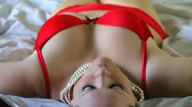 donna sdraiata supina con collana di perle e lingerie rossa