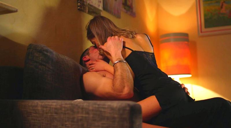 uomo e donna seminudi che si baciano seduti sul divano con donna in braccio all'uomo