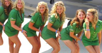 sei hostess sexy con divisa verde che si toccano il sedere