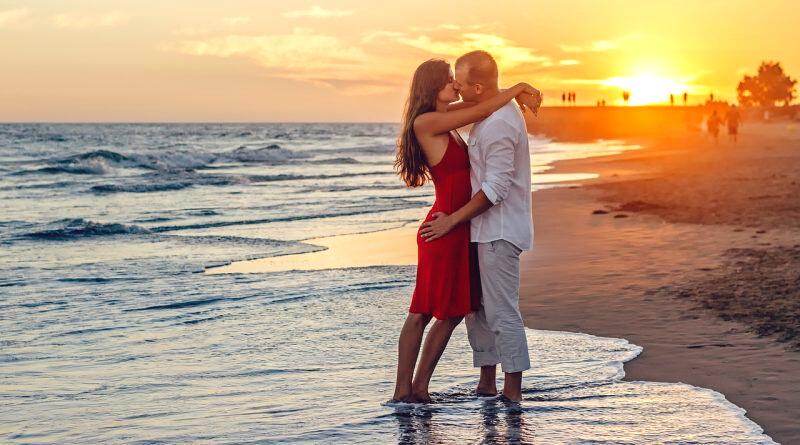coppia che si abbraccia e si bacia in riva al mare con il tramonto alle spalle