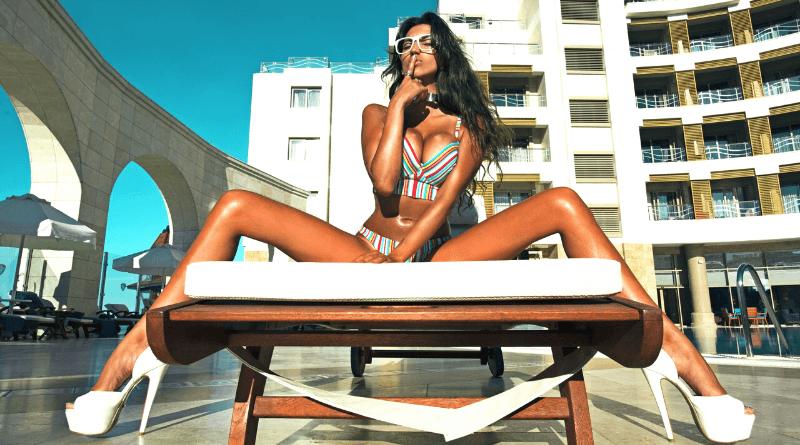 donna in costume e occhiali da sole seduta a gambe divaricate sul lettino sdraio di un hotel