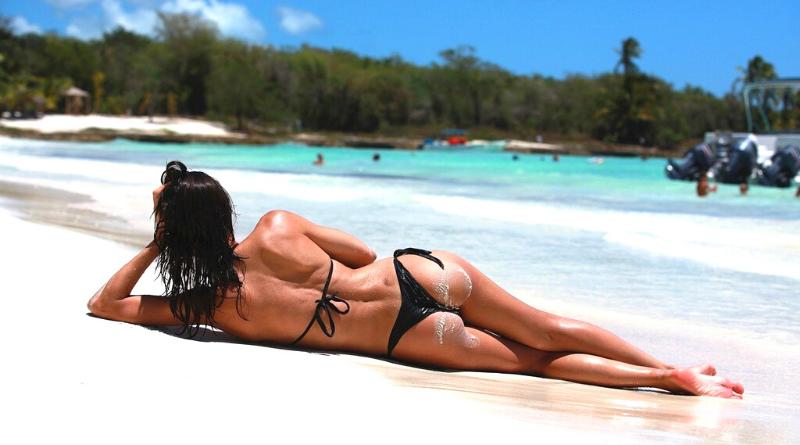donna in costume nero sdraiata sul fianco su riva con spiaggia bianca