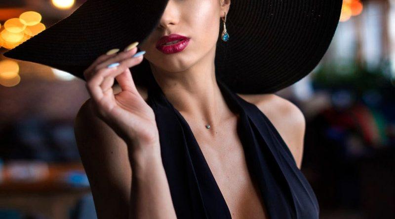 donna di classe con grande cappello e vestito nero su fondo notte