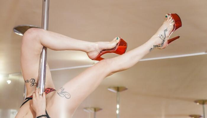 gambe di donna con tacchi rossi che balla su palo in locali hot