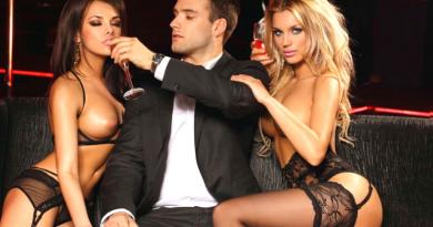 uomo elegante fra due donne bellissime in lingerie sexy seduti su divano in pelle nero in locale trasgressivo