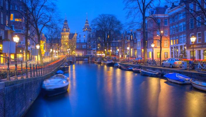Amsterdam di notte che si riflette in un fiume