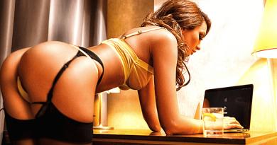 donna in lingerie piegata con gomiti appoggiati alla scrivania che utilizza PC