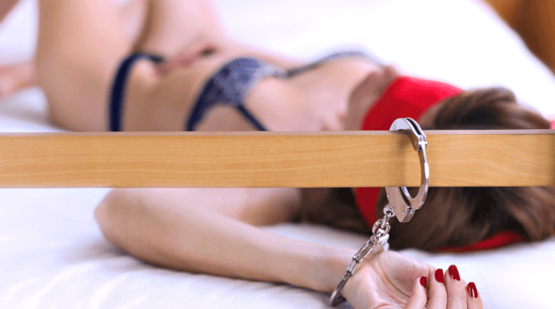 donna ammanettata sul letto con benda rossa