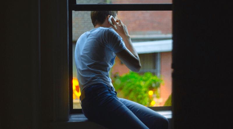 uomo di spalle affacciato alla finestra che ascolta frasi sexy per lui al cellulare