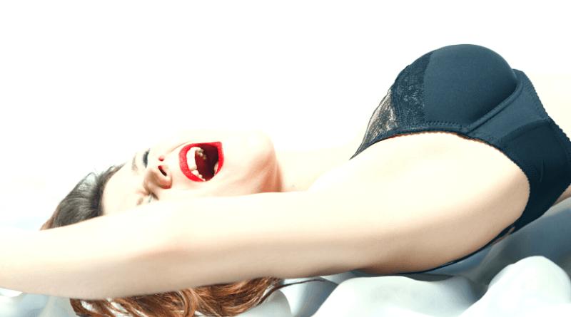 donna di profilo con braccia alzate con espressione di goduria