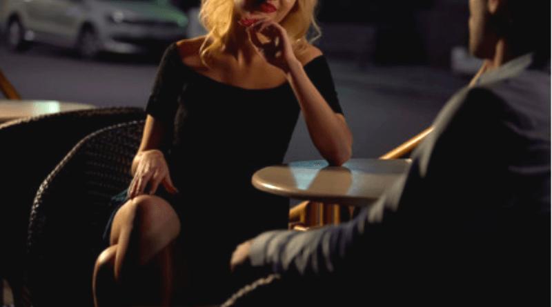 donna provocante seduta con uomo al tavolino di un bar